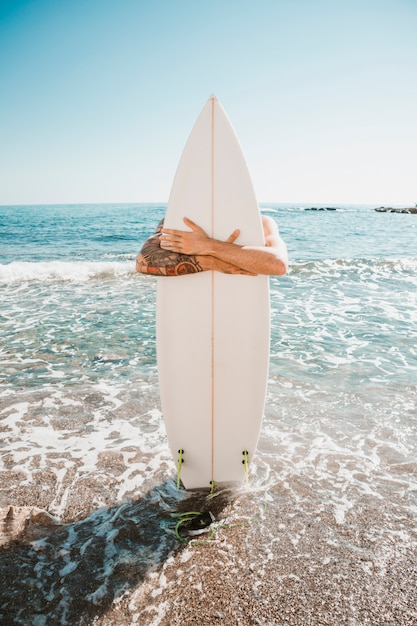 Man with surf board on beach near sea Free Photo