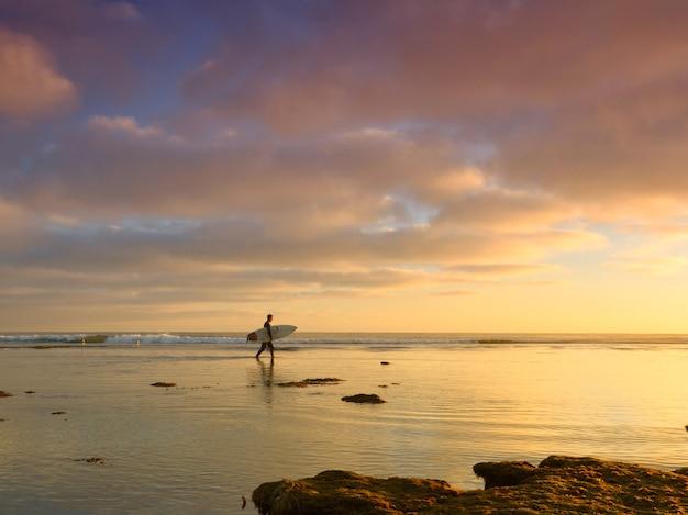 Uomo con tavola da surf in un mare con un bel tramonto Foto Gratuite