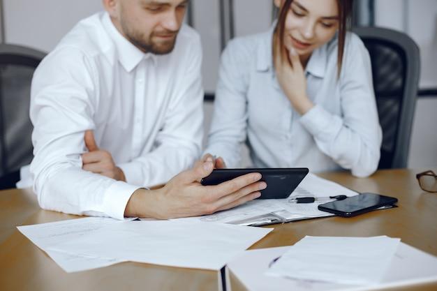 Uomo con una tavoletta. partner commerciali a una riunione di lavoro persone sedute al tavolo Foto Gratuite