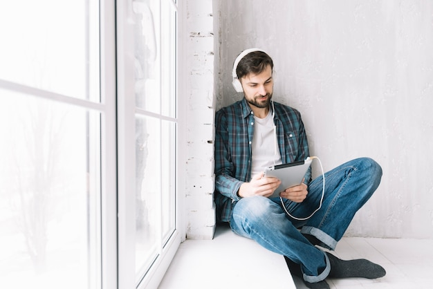 Man with tablet relaxing near window Free Photo