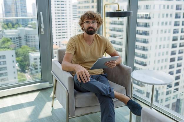 近代的なオフィスのソファーに座っているタブレットを持つ男。 無料写真