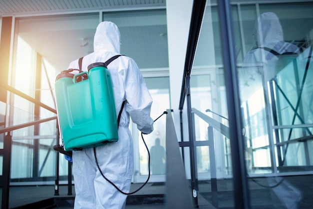 Man with tank reservoir on his back spraying disinfectant to stop corona virus Free Photo
