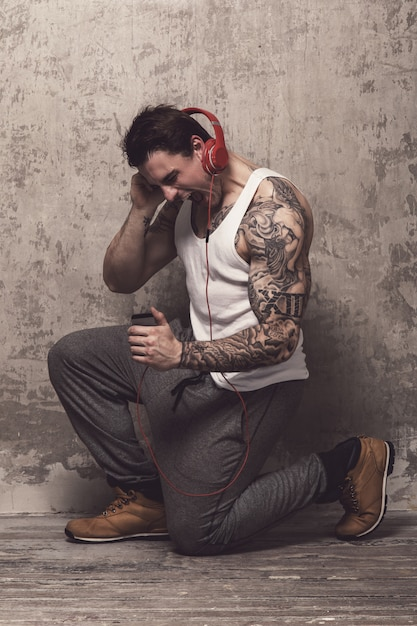Man with tattoo listening to music Free Photo