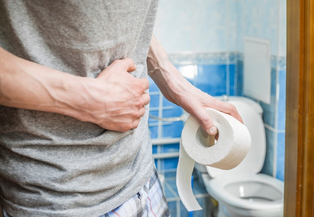 A man with toilet paper clings to his stomach. diarrhea. Premium Photo