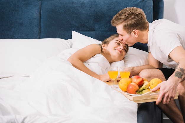 Man with tray of food kissing sleeping woman onforehead Free Photo