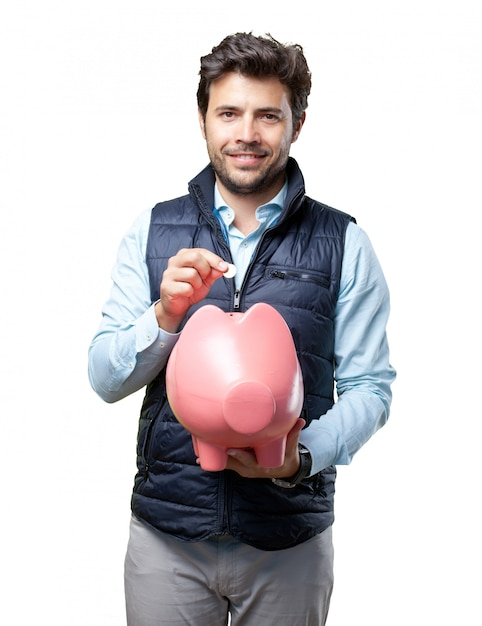 Man with vest insert coin on pig Premium Photo