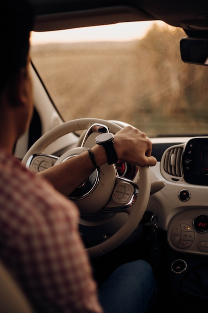 Man with watch driving a car Premium Photo