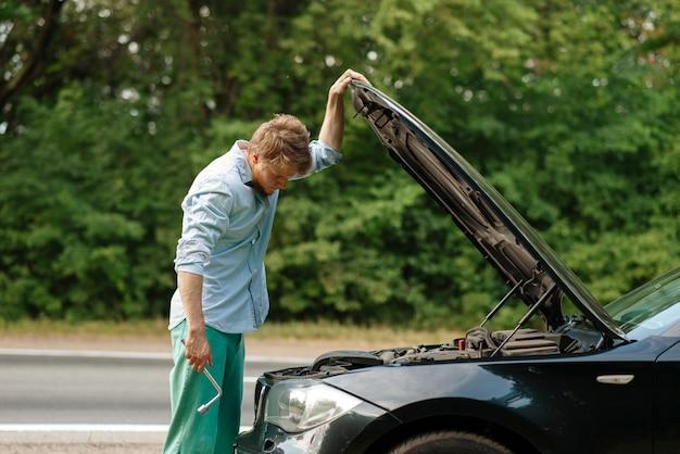 Man with wheel brace standing at the opened hood, car breakdown. Premium Photo