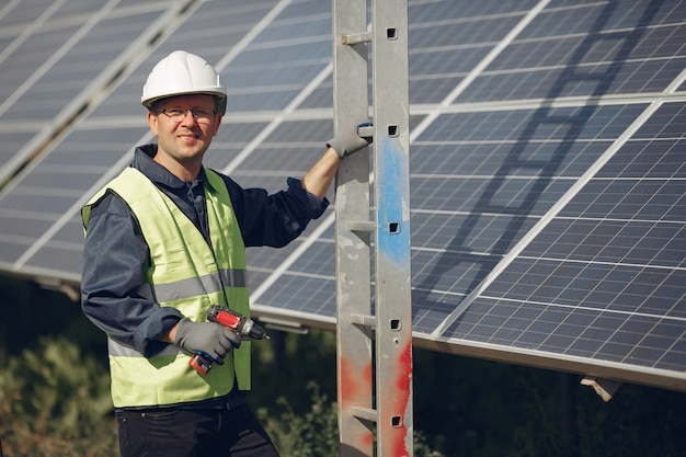 Man with white helmet near a solar panel Free Photo