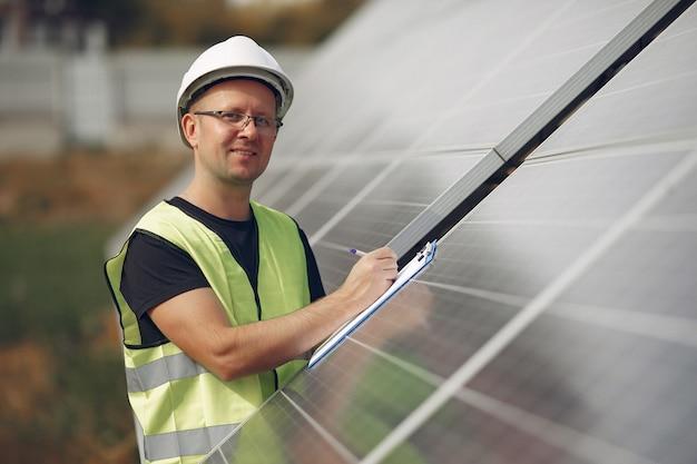 Man with white helmet near a solar panel Free Photo