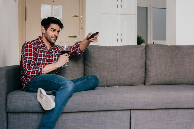 Man with wine on couch Free Photo