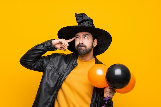 Man with witch hat holding black and orange air balloons for ...