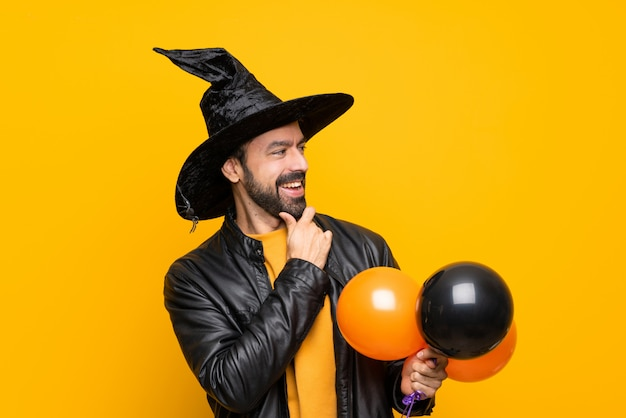 Man with witch hat holding black and orange air balloons for halloween party looking to the side Premium Photo