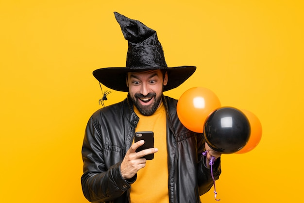 Man with witch hat holding black and orange air balloons for halloween party surprised and sending a message Premium Photo