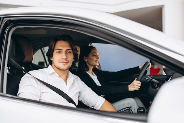 Man with woman in a car showroom choosing a car Free Photo