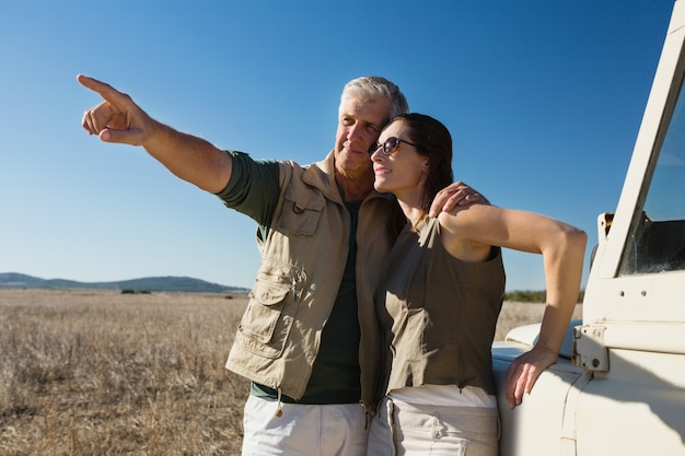 Man with woman pointing by vehicle on field Free Photo