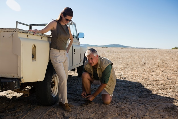 Man with woman tying shoelace by vehicle on field Free Photo