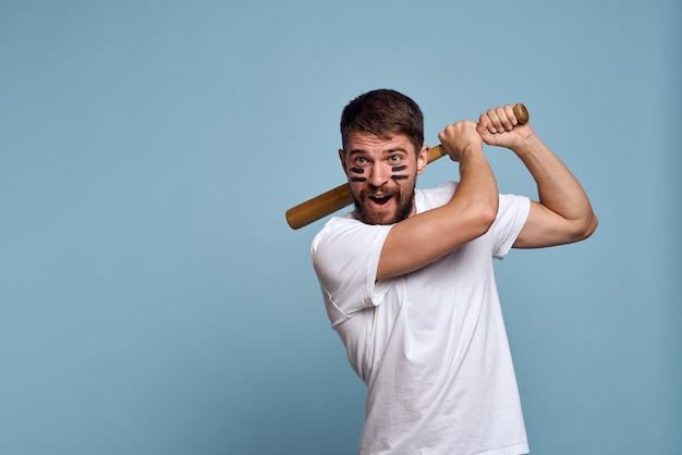A man with a wooden bat and black lines on his face blue background white t-shirt Premium Photo