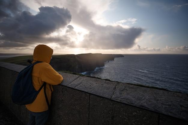 モハーの断崖の地平線を見て黄色のジャケットの男 Premium写真