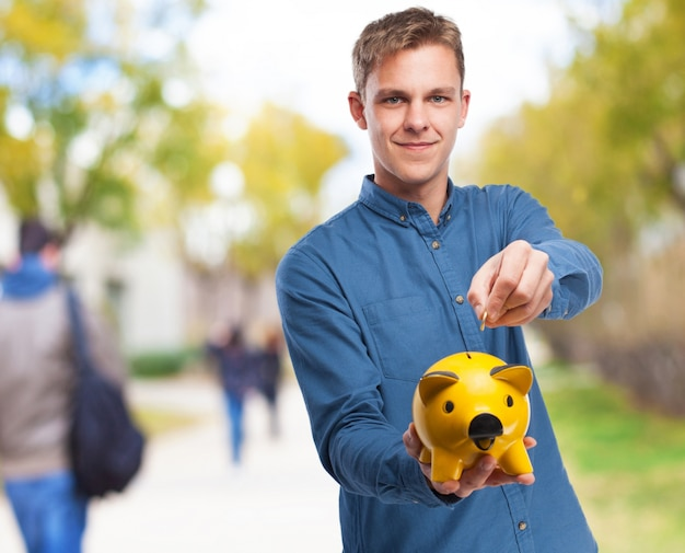 Man with a yellow piggy bank Free Photo