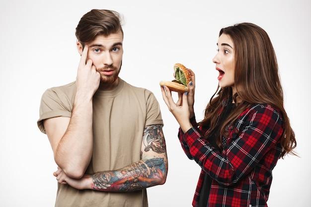 Мужчина, женщина раздражает парня, играет с бургером. Бесплатные Фотографии