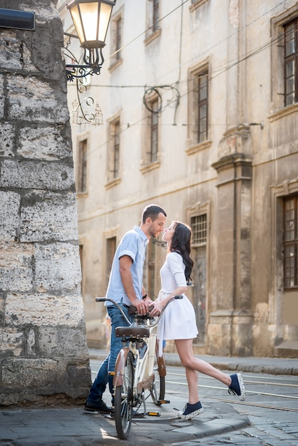 Man and woman are drawn to each other that would kiss near retro tandem bike in urban environment on the narrow old streets Premium Photo