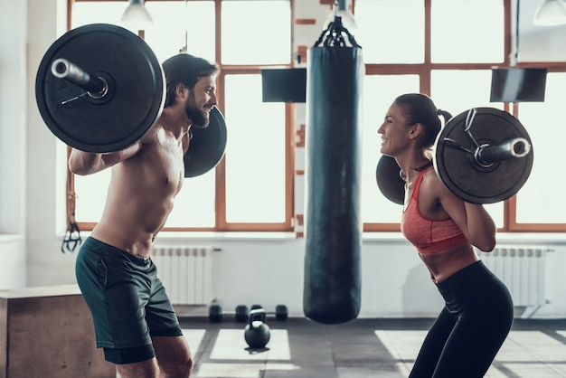 Man and woman are lifting barbells in the gym. Premium Photo