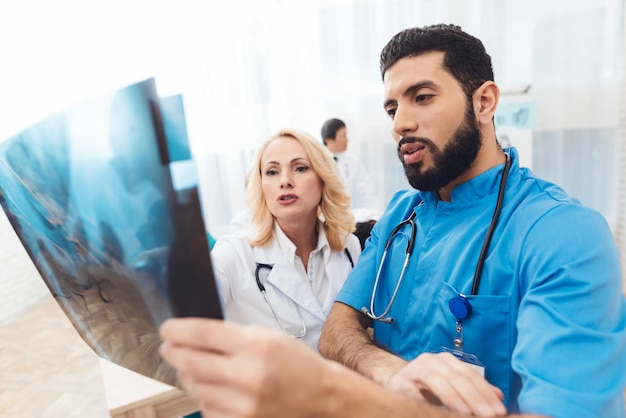 A man and a woman are looking at the x-ray of the pelvis. Premium Photo