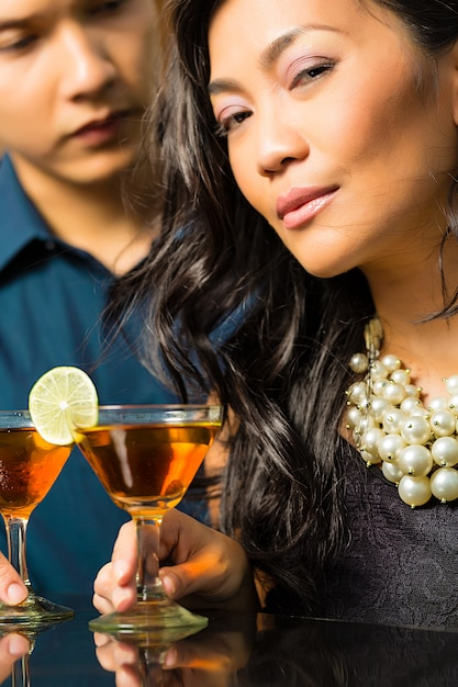 Man and woman in asia at bar with cocktails Premium Photo