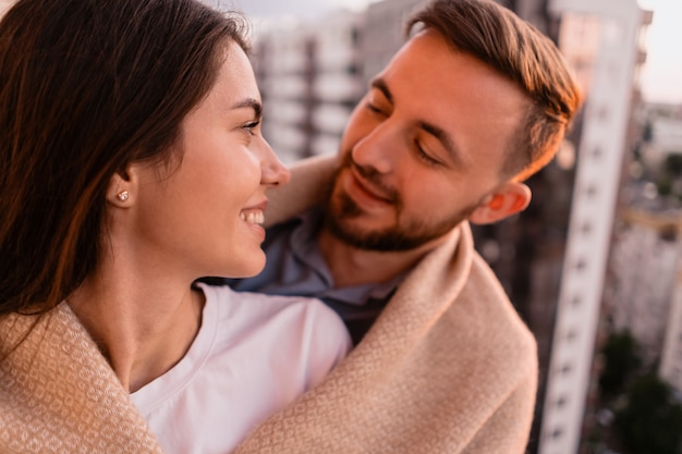 Man and woman on balcony at sunset in the city Free Photo