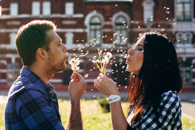Man and woman blowing dandelions on each other Premium Photo