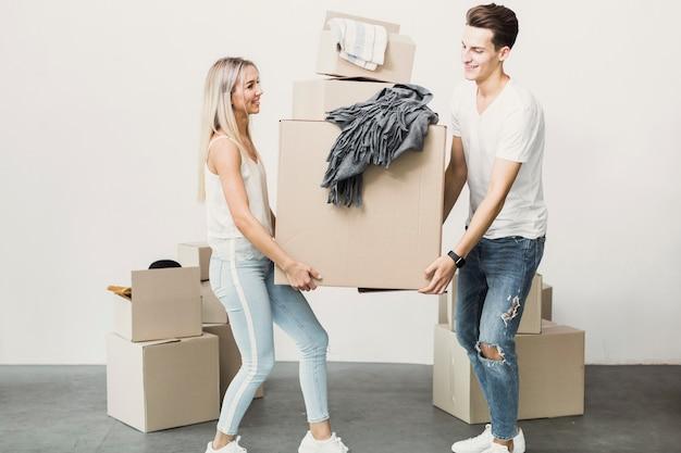 Man and woman carrying carton box Free Photo