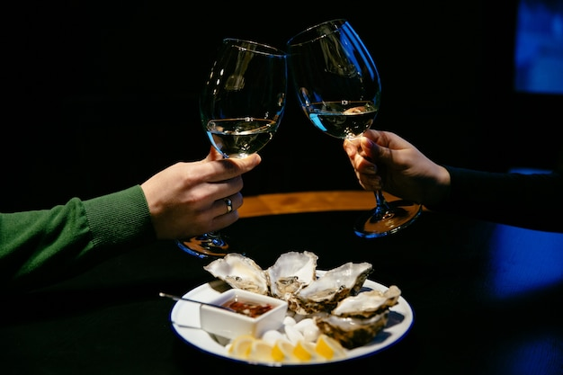 Man and woman do a cheers with champagne glasses. Free Photo