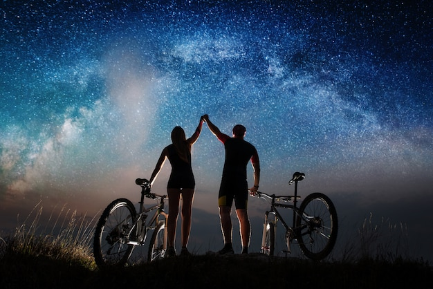 Man and woman cyclists with mountain bikes keep the hands lifted upwards to sky on the hill. Premium Photo