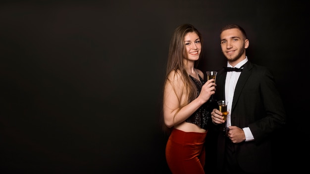 Man and woman in dinner jacket and evening wear with glasses of drinks Free Photo