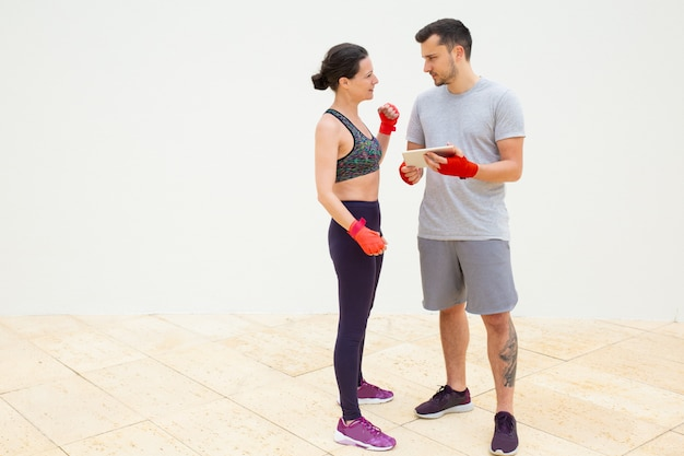 Man and woman discussing training plan with wrapped hands Free Photo