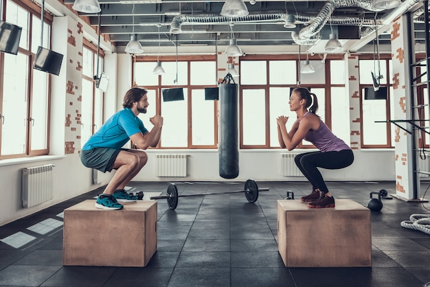 Man and woman doing squats on wood blocks in gym. Premium Photo