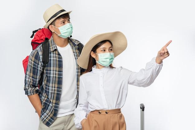 Uomo e donna vestiti per viaggiare, che indossano maschere insieme ai bagagli Foto Gratuite