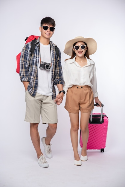 Uomo e donna vestiti con gli occhiali per viaggiare con le valigie Foto Gratuite