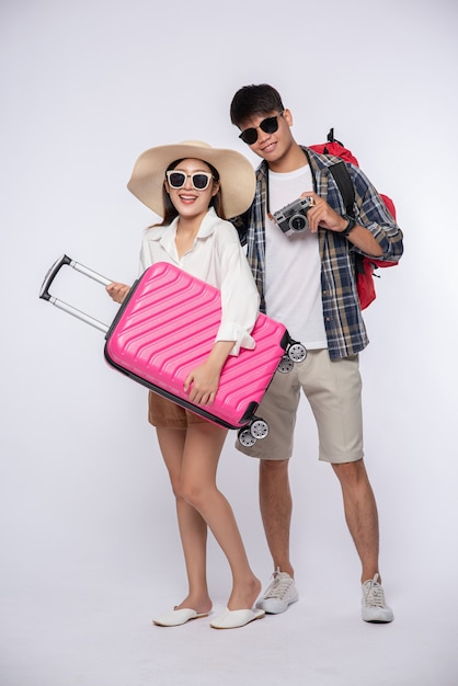 Man and woman dressed up wearing glasses to travel with suitcases Free Photo
