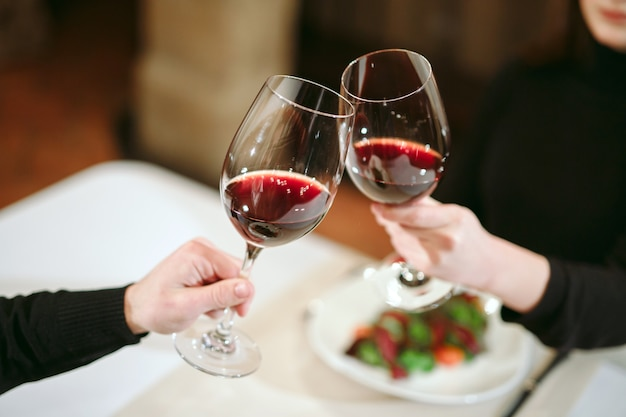 Man and woman drinking red wine. in the picture, close-up hands with glasses. Premium Photo