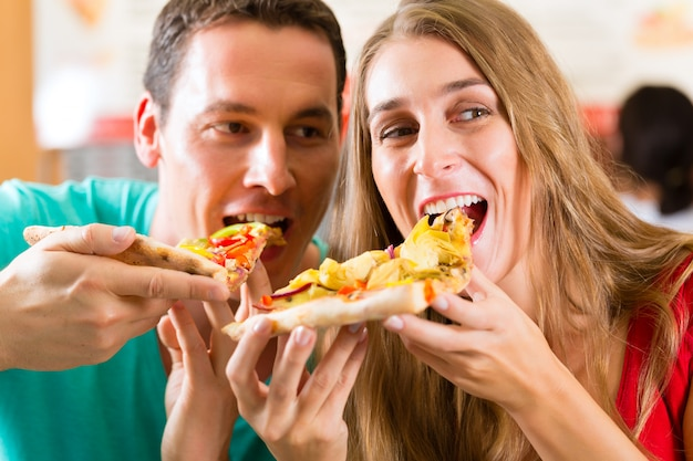 Man and woman eating a pizza Premium Photo