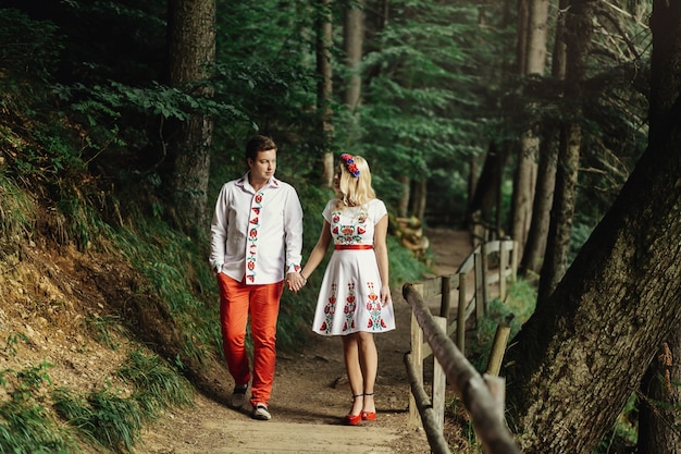 Man and woman in embroidered clothes walk along wooden path in the forest Free Photo
