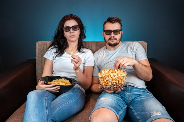 A man and a woman, a family watching a movie or a series in 3d glasses, a blue wall. the concept of a cinema, films, emotions, surprise, leisure, streaming platforms. Premium Photo