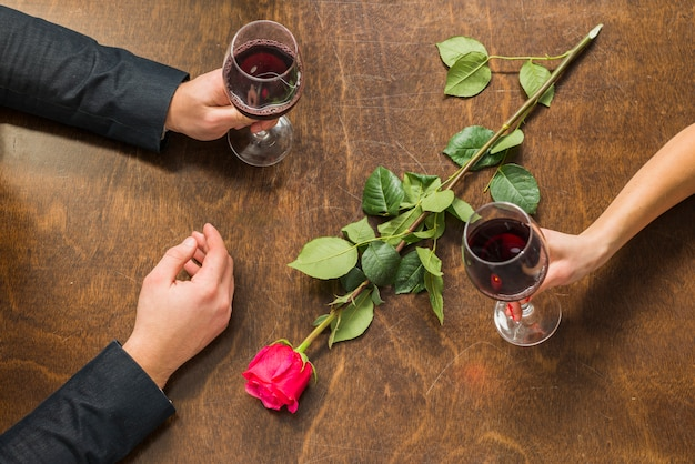 Man and woman hands at table with glasses and flower Free Photo