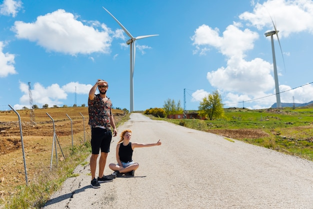Man and woman hitchhiking on road Free Photo