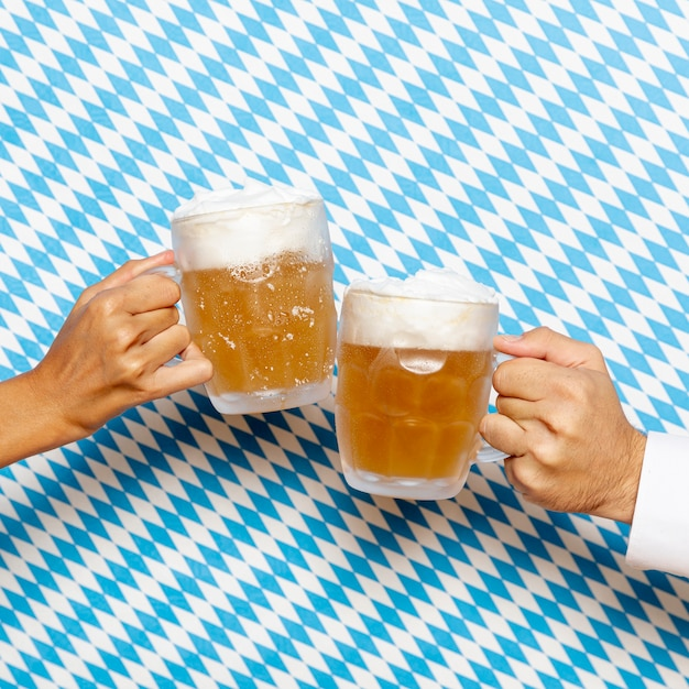 Man and woman holding beer pints Free Photo