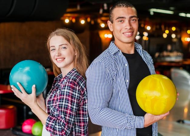 Uomo e donna che tengono le palle da bowling Foto Gratuite