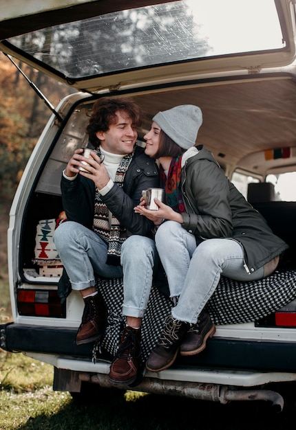 Man and woman holding cups of coffee in a van Premium Photo