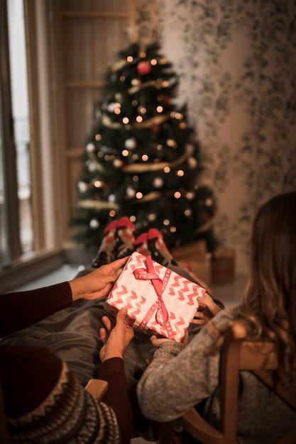Man and woman holding gift box on chairs near christmas tree Free Photo
